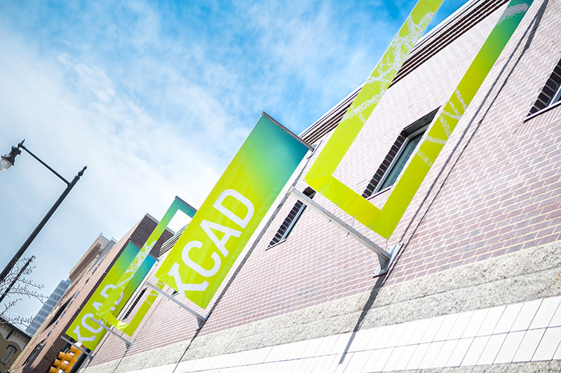 Rectangular banners with the kay cad logo hanging on the side of a building