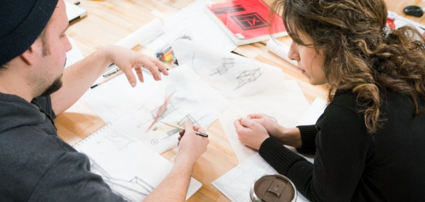 Two students sketching on a piece of paper
