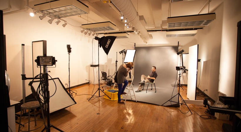 Person staging a photo shoot in a lighting studio