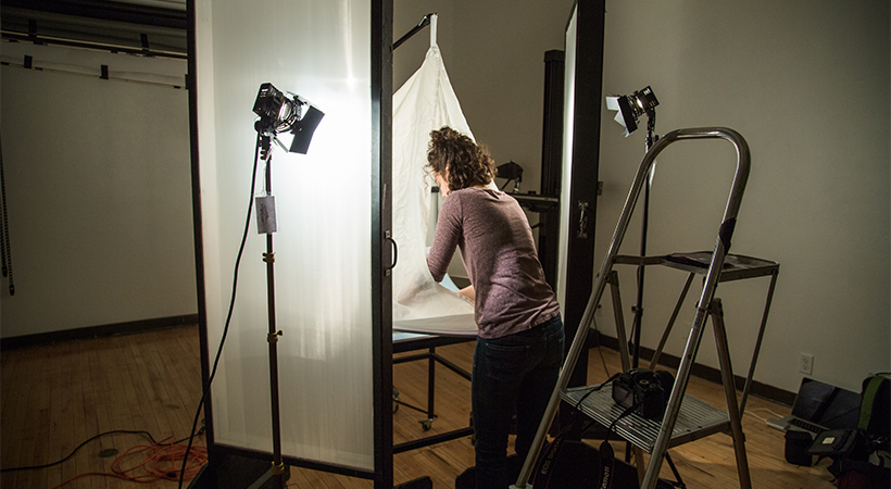 Woman staging a photo shoot on a white background