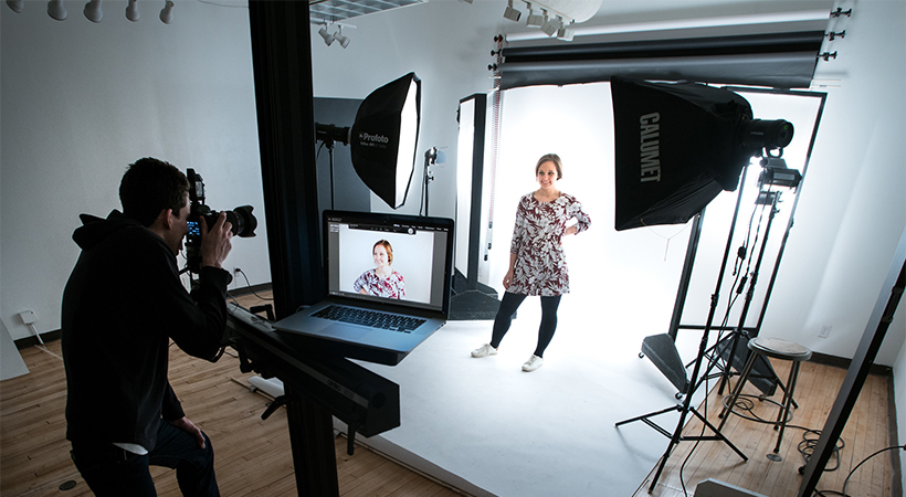 Man taking a picture of a model in a photography studio