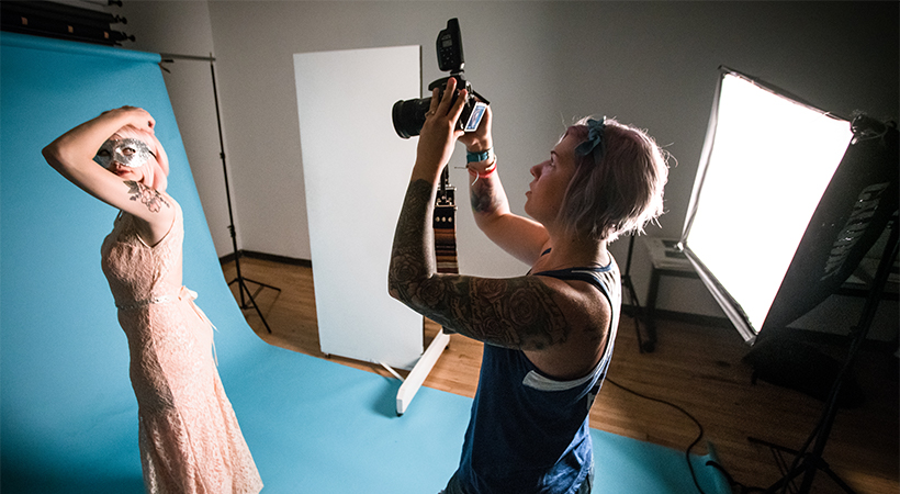 Woman taking a picture of a model in a photography studio