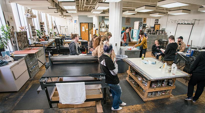Group of people using large printmaking equipment