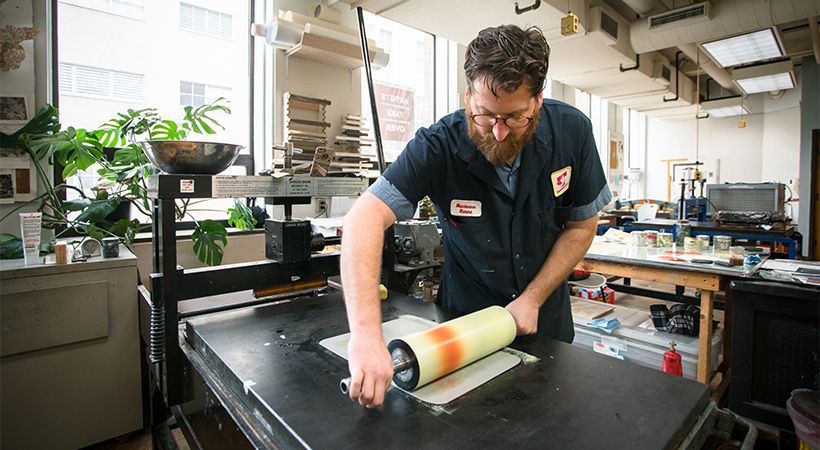 A man rolling ink onto a piece of paper