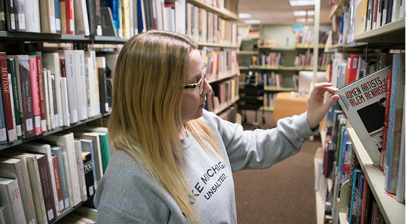 Woman pulling a book from the shelves of a library