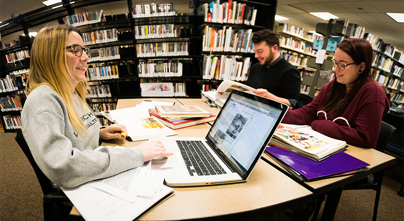 Students working together at a table in a library