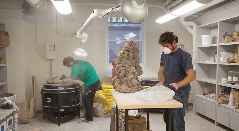Two men work with clay in a mixing machine