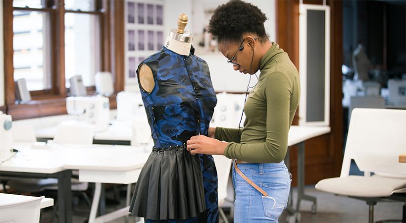 A woman pins a garment onto a dress form