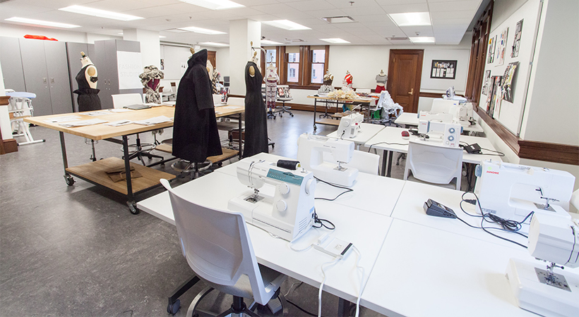 A classroom filled with sewing machines and dress forms