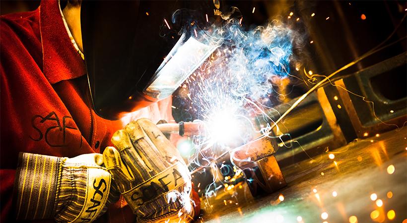 A person in a welding helmet welding