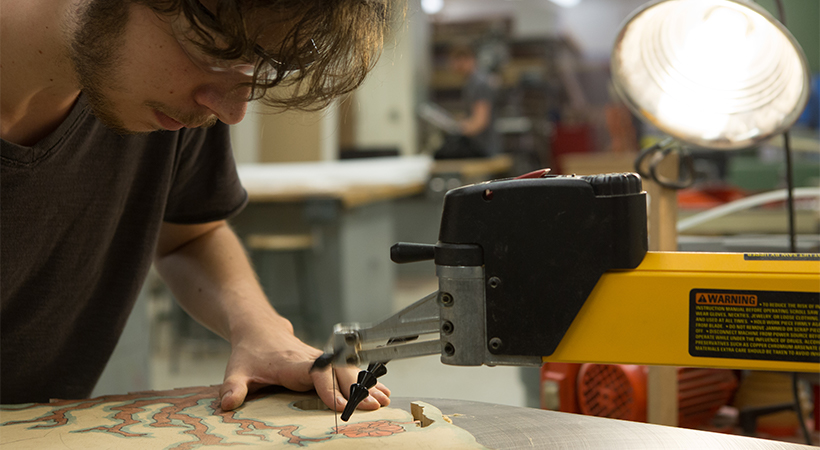 A man using a band saw to cut out a custom shape from a piece of wood