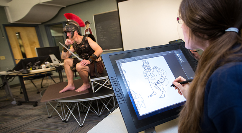 A woman sketches a man dressed as a Roman soldier on a digital drawing tablet
