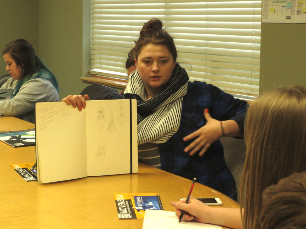 Junior Krystal Peto shows her sketches to Patricia Barker