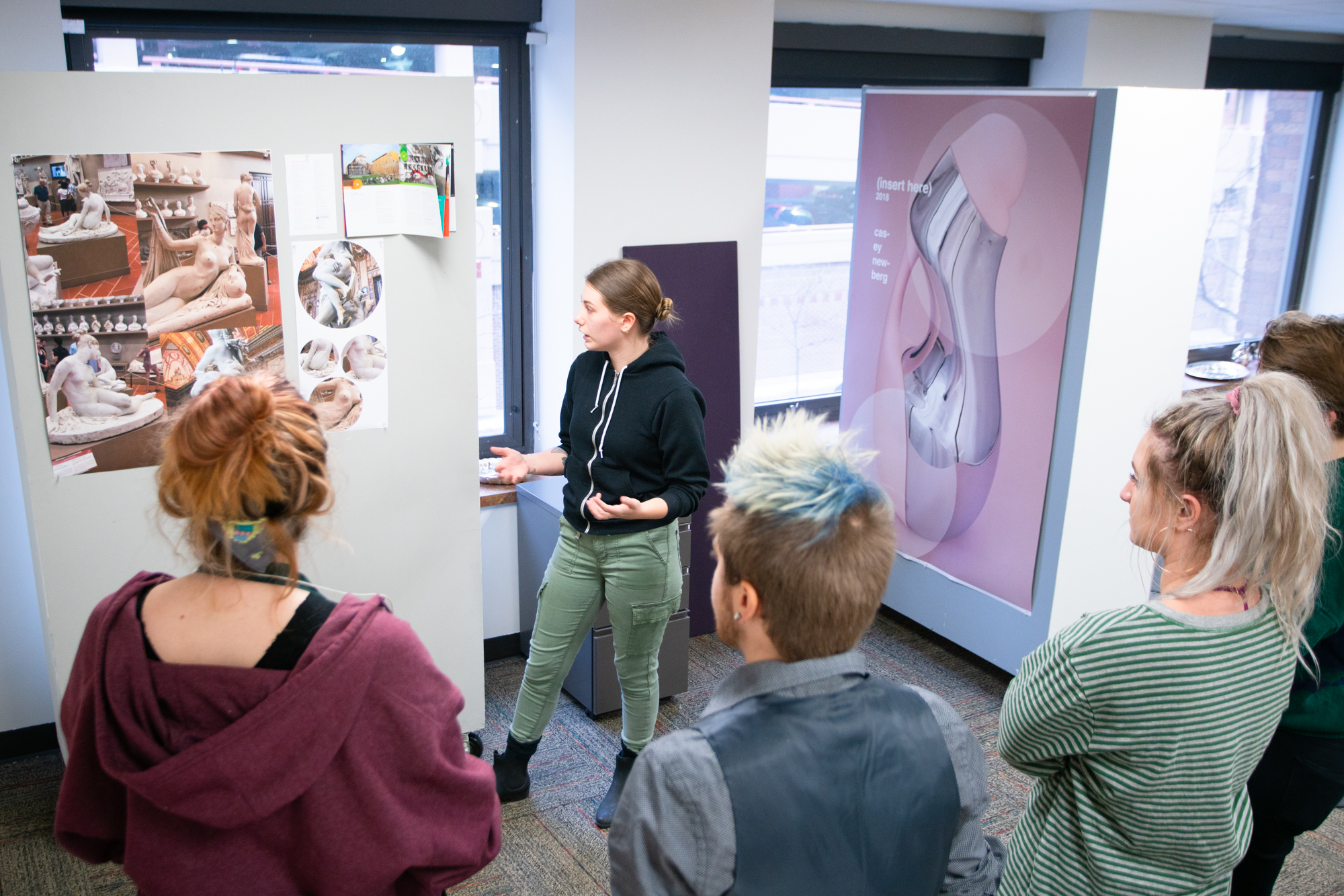 Woman talking to a group of people as she gestures toward a graphic hanging on the all