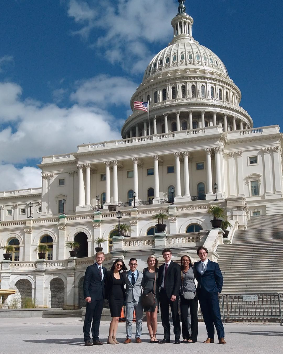 Group of people posing in front of the Capitol Building in Washington D.C.
