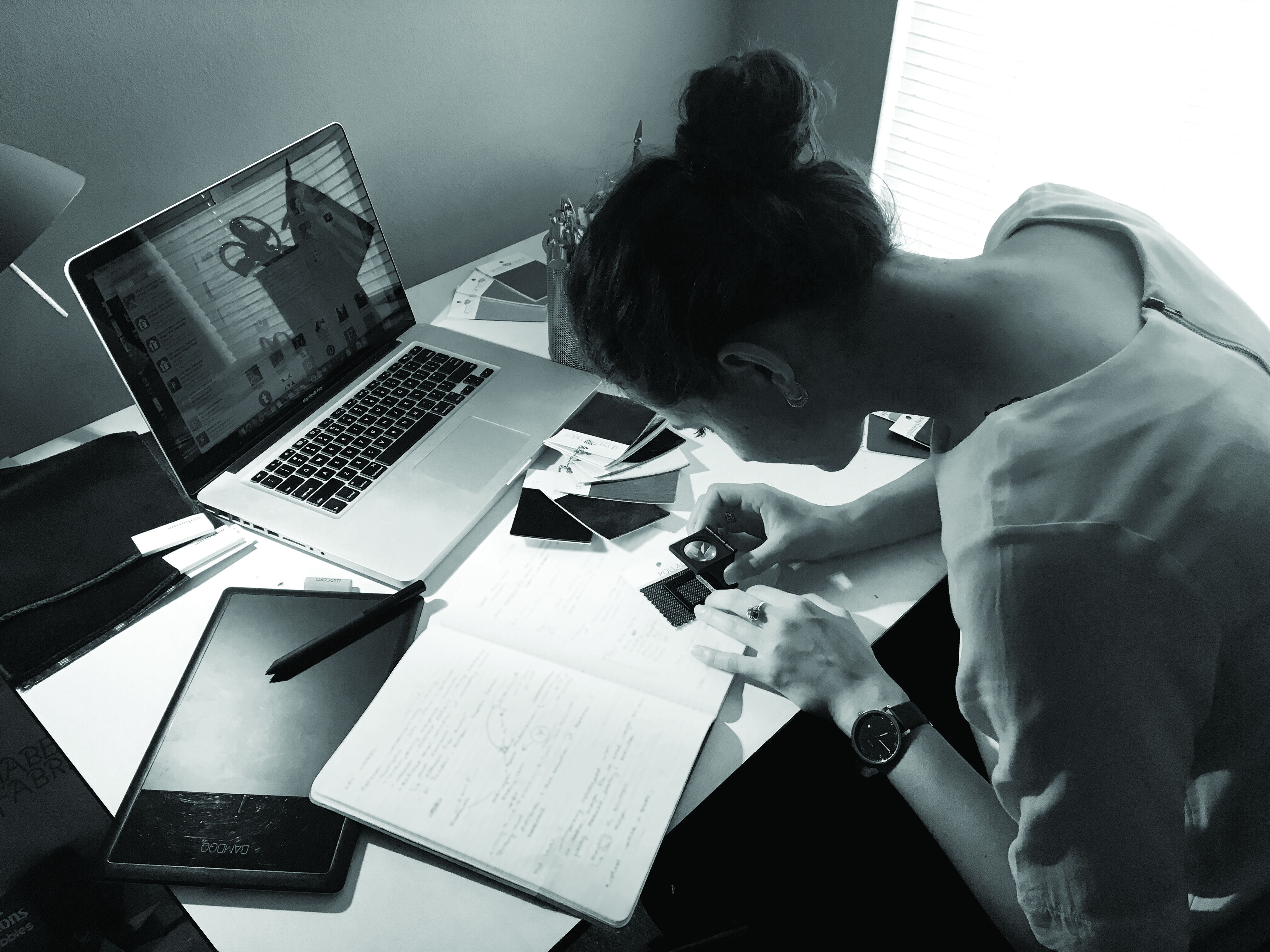Woman hunched over a desk sketching
