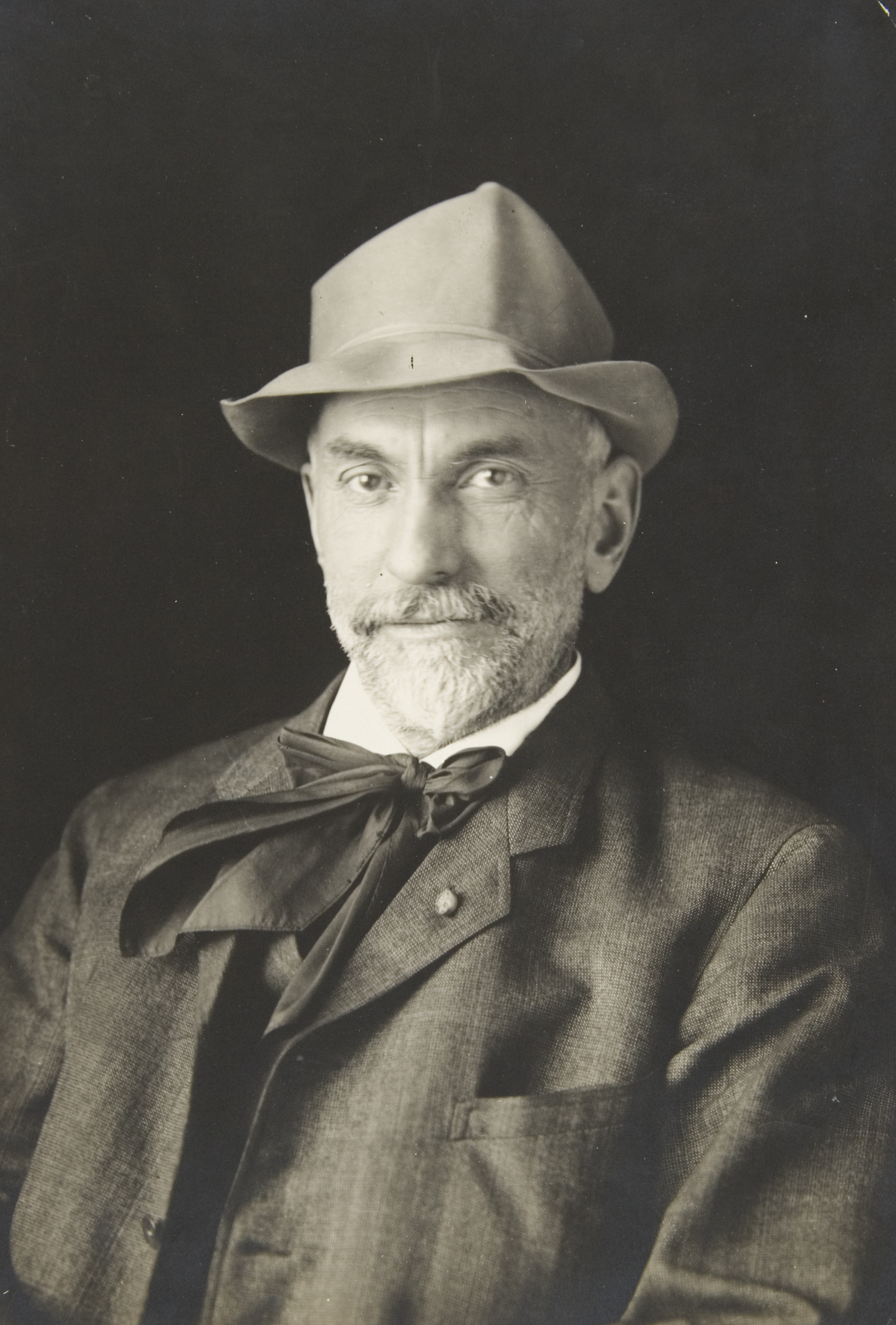 Old portrait photo of distinguished man with hat