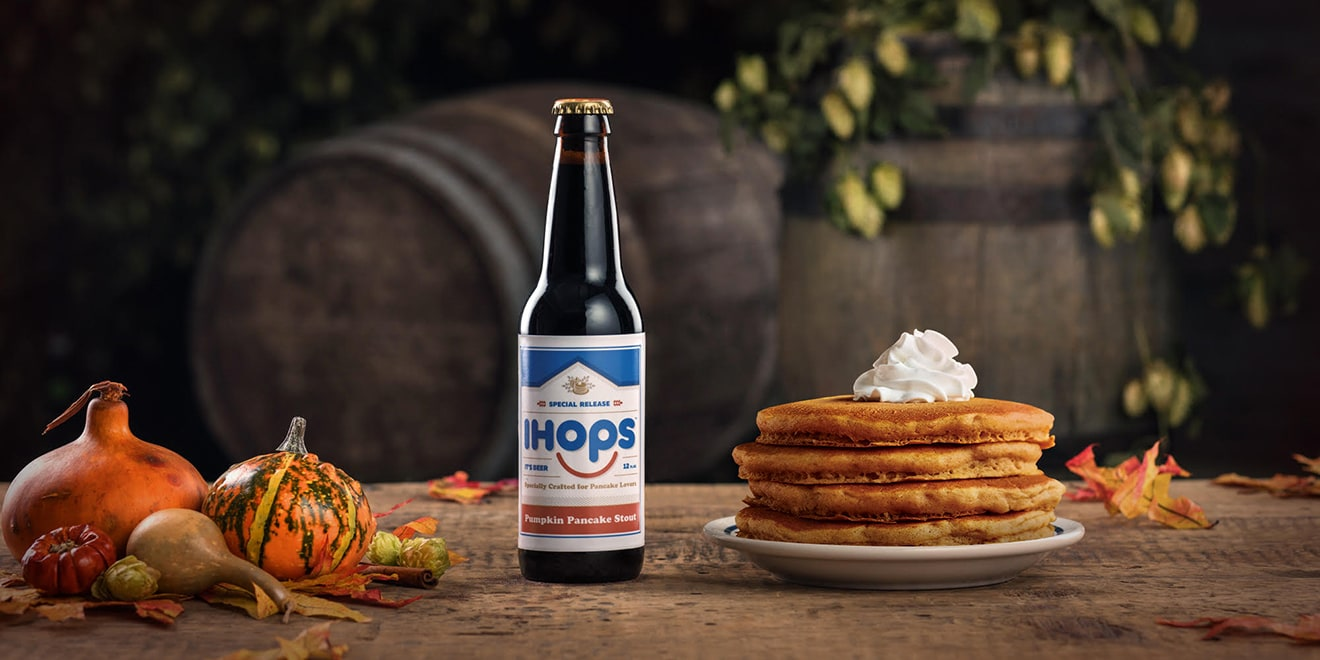 Bottle of beer next to stack of pancakes