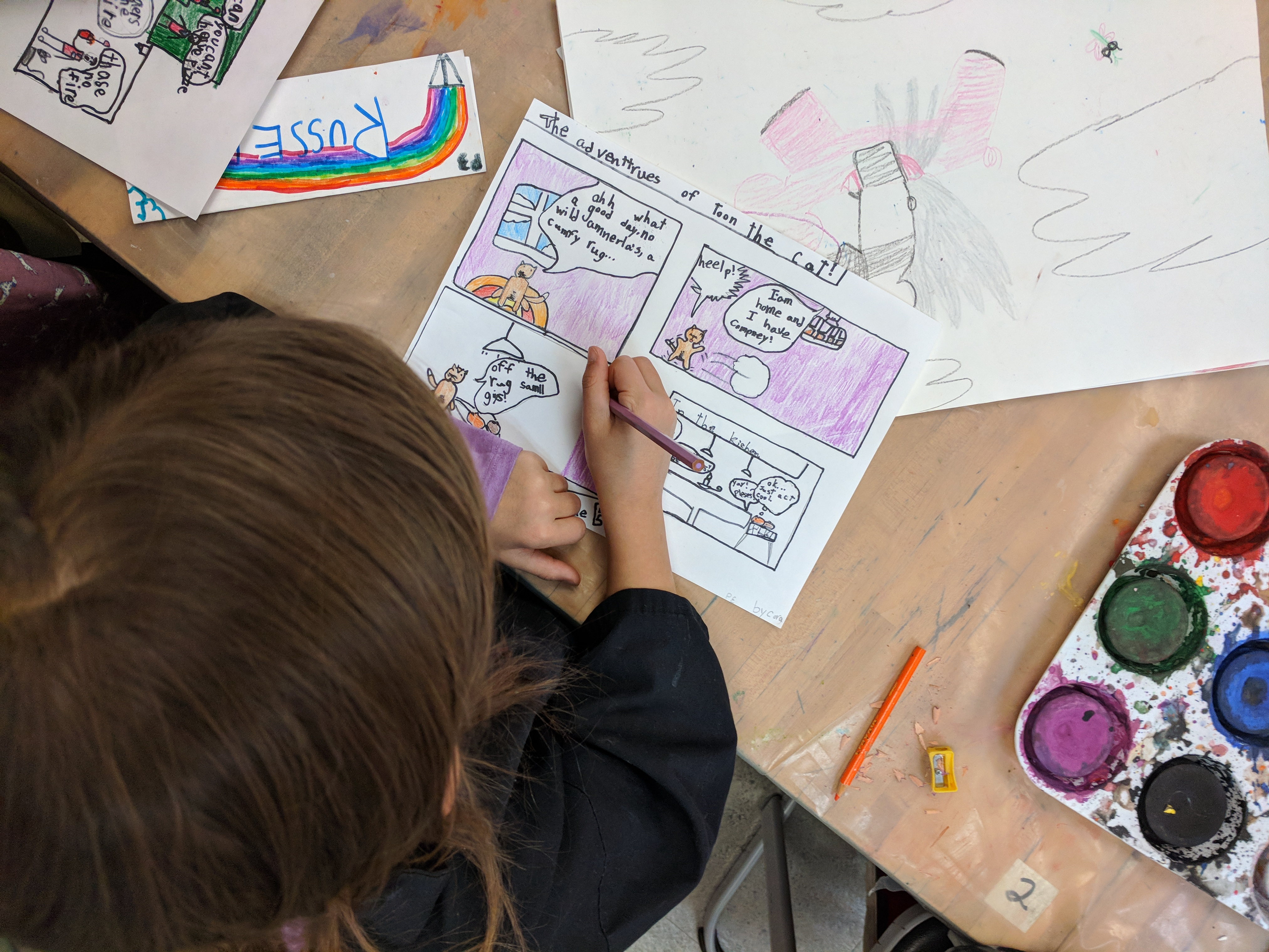A young girl creating a comic strip in an art class