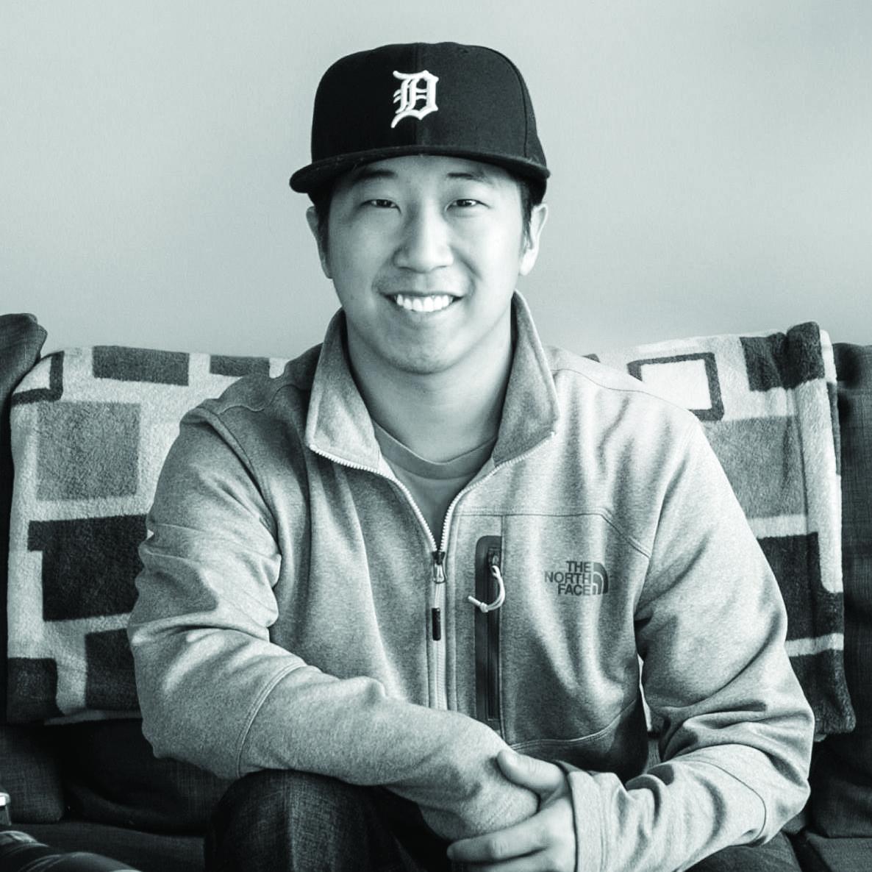 Man wearing a baseball cap smiling at the camera