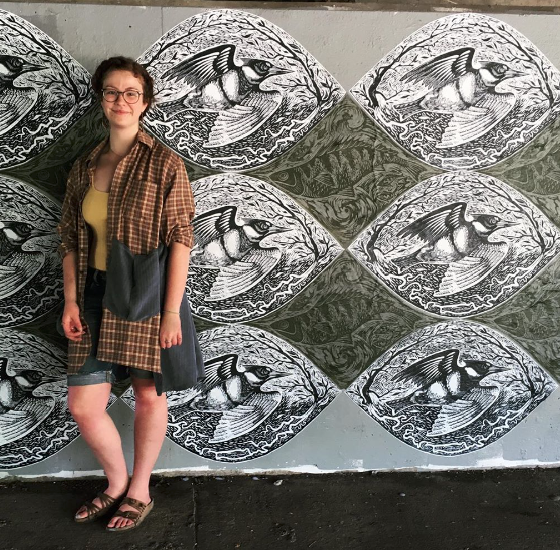 Woman standing next to a mural of a river