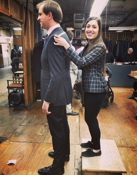 A woman stands behind a man measuring him for a custom fitted suit