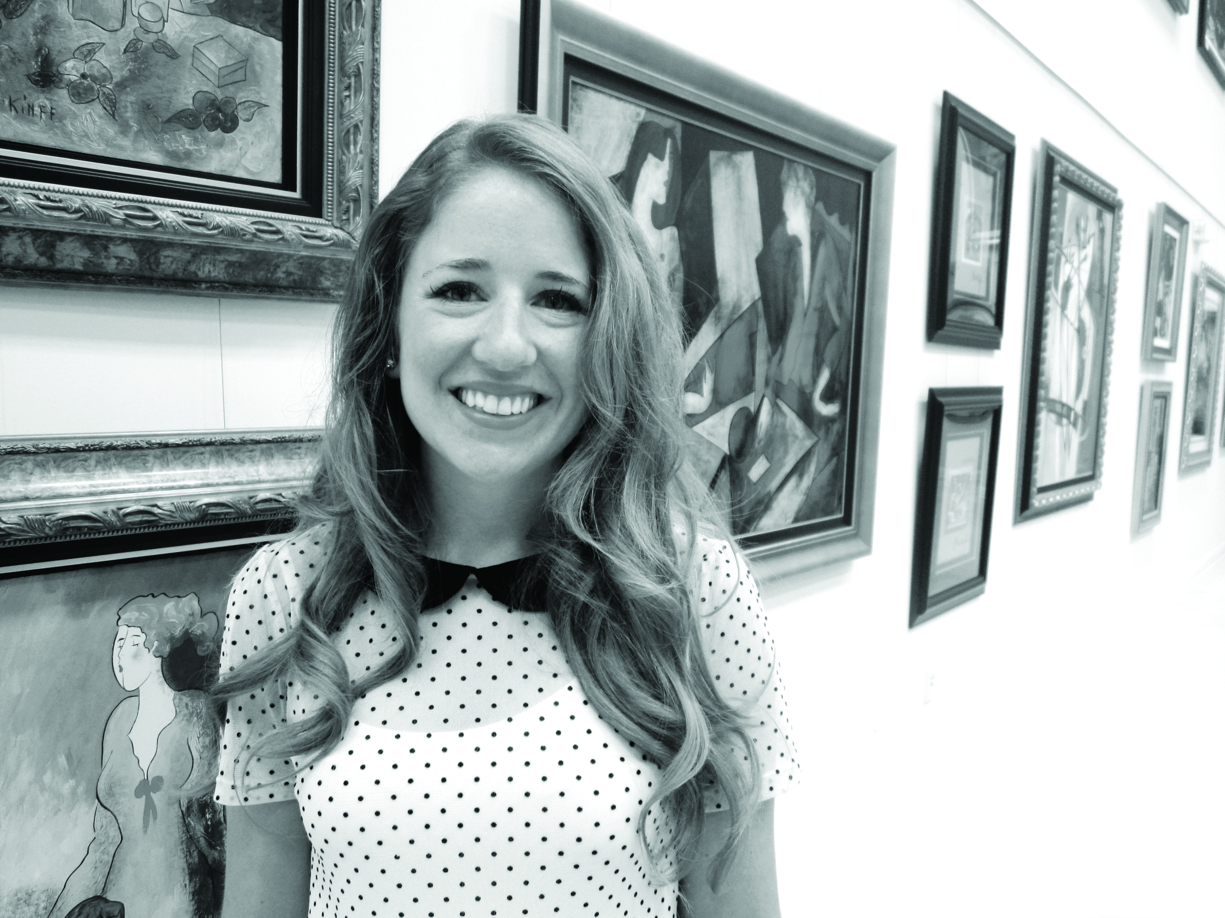 Woman wearing a dotted shirt stands in front of an art gallery wall and smiles at the camera