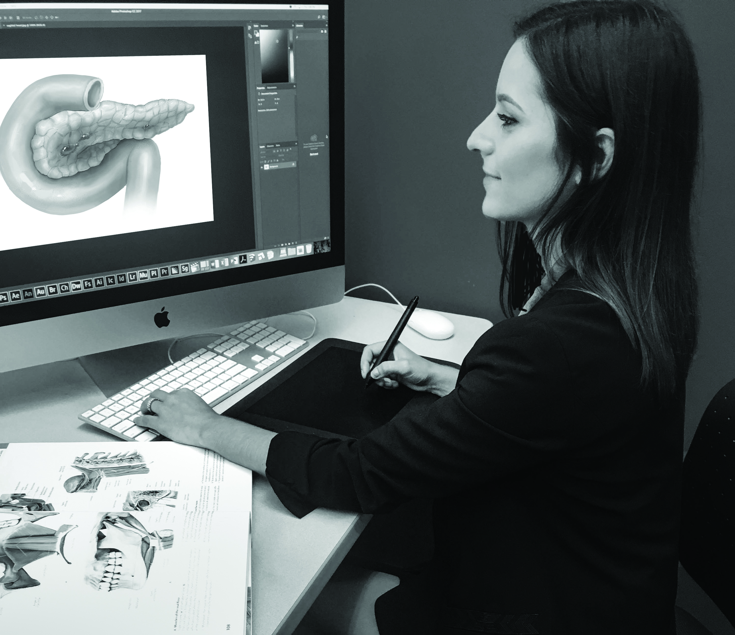 Women sitting at her computer creating an digital illustration of the human body