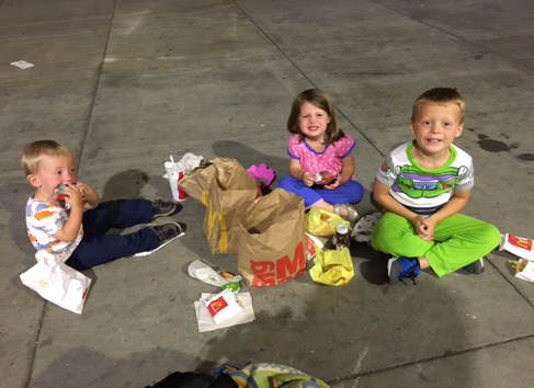 Kids wait at the airport eating dinner