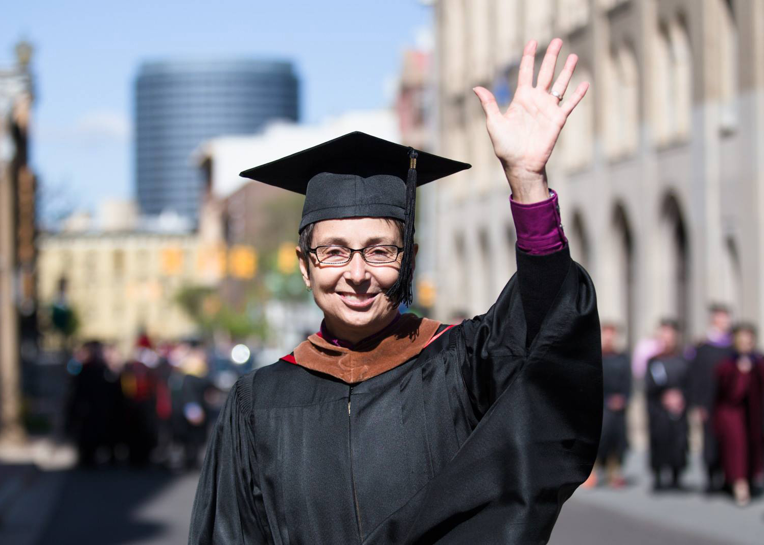 Woman in a graduation cap and gown waves at the camera