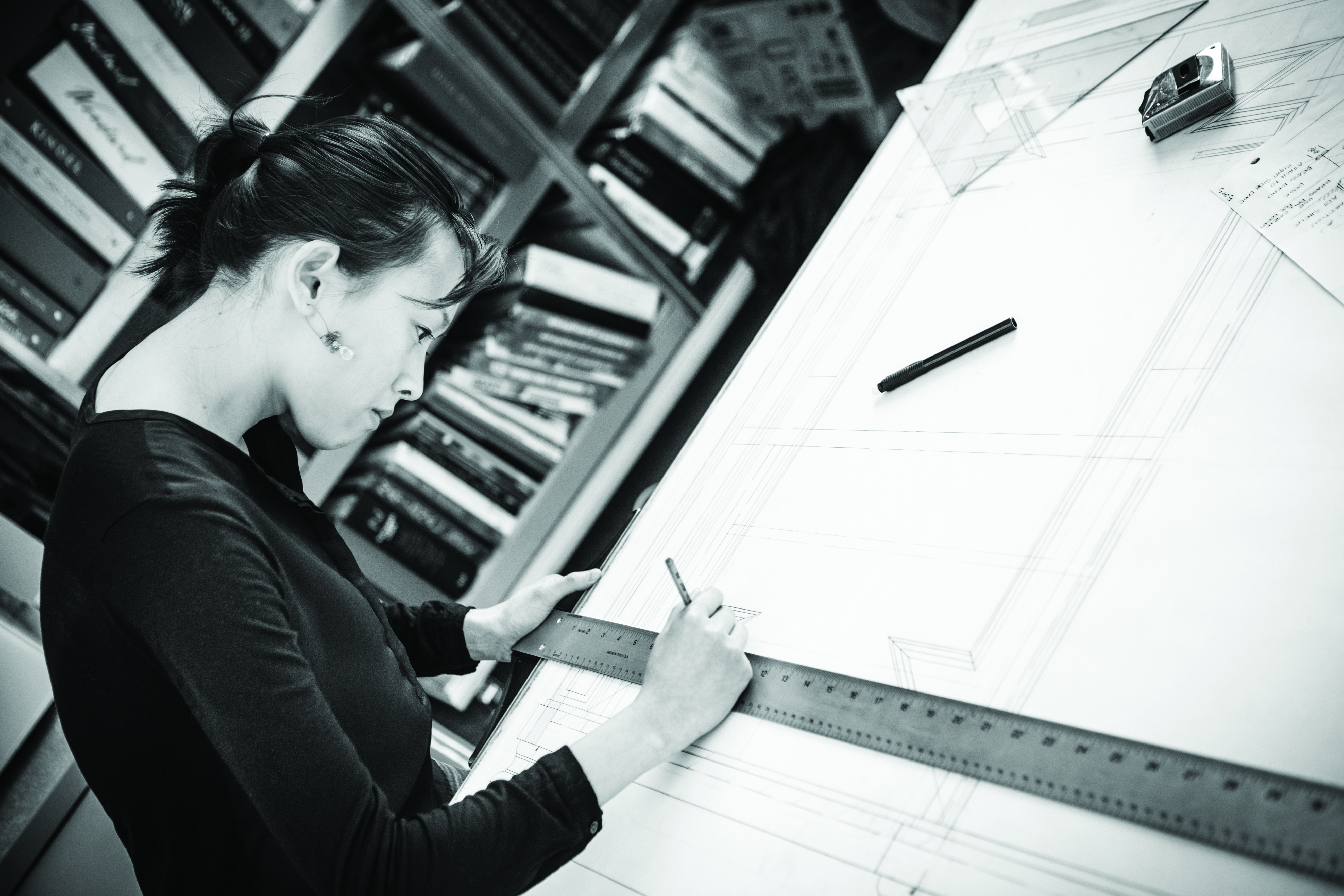 Woman staring concentratedly at a drafting table as she uses a ruler to draw a straight line on a design
