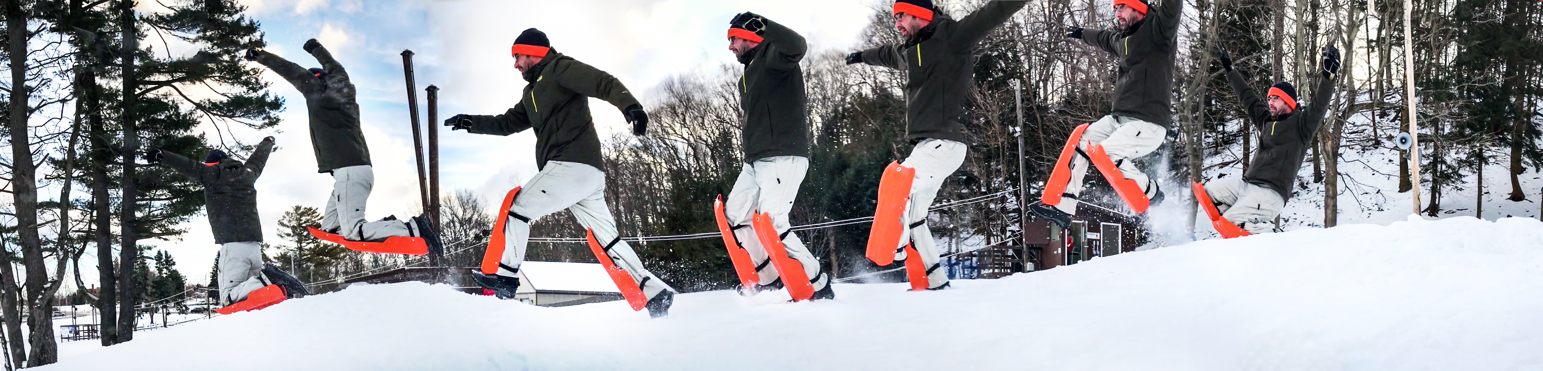 Man wearing skis on his knees leaps into winter fun