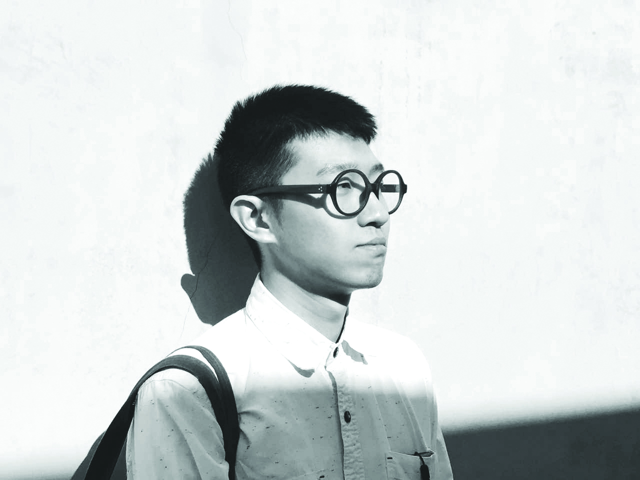 Man in circle rimmed glasses stands up against a wall and looks off into the distance