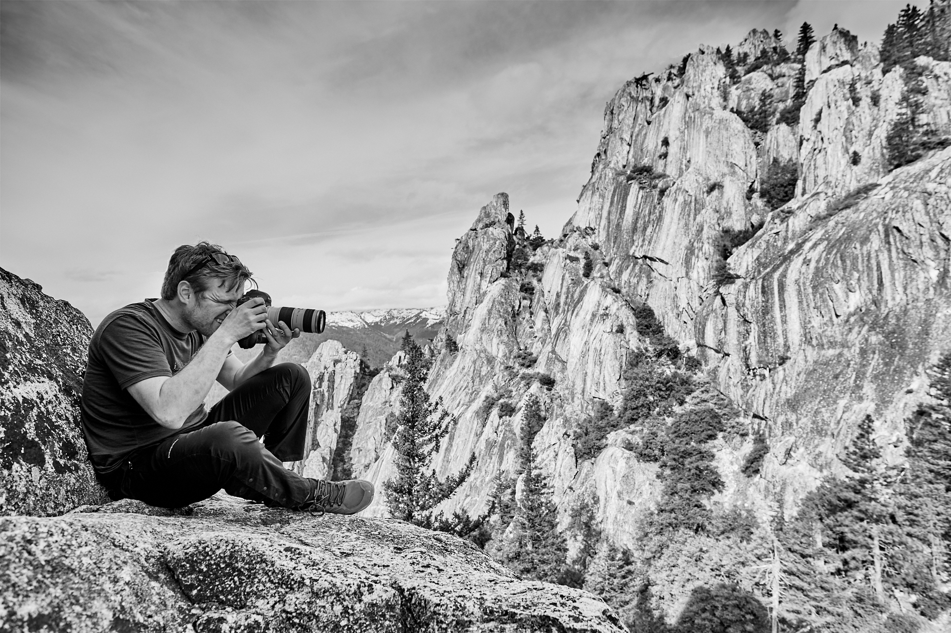 Man sitting on the side of a mountain aiming a camera out of the frame