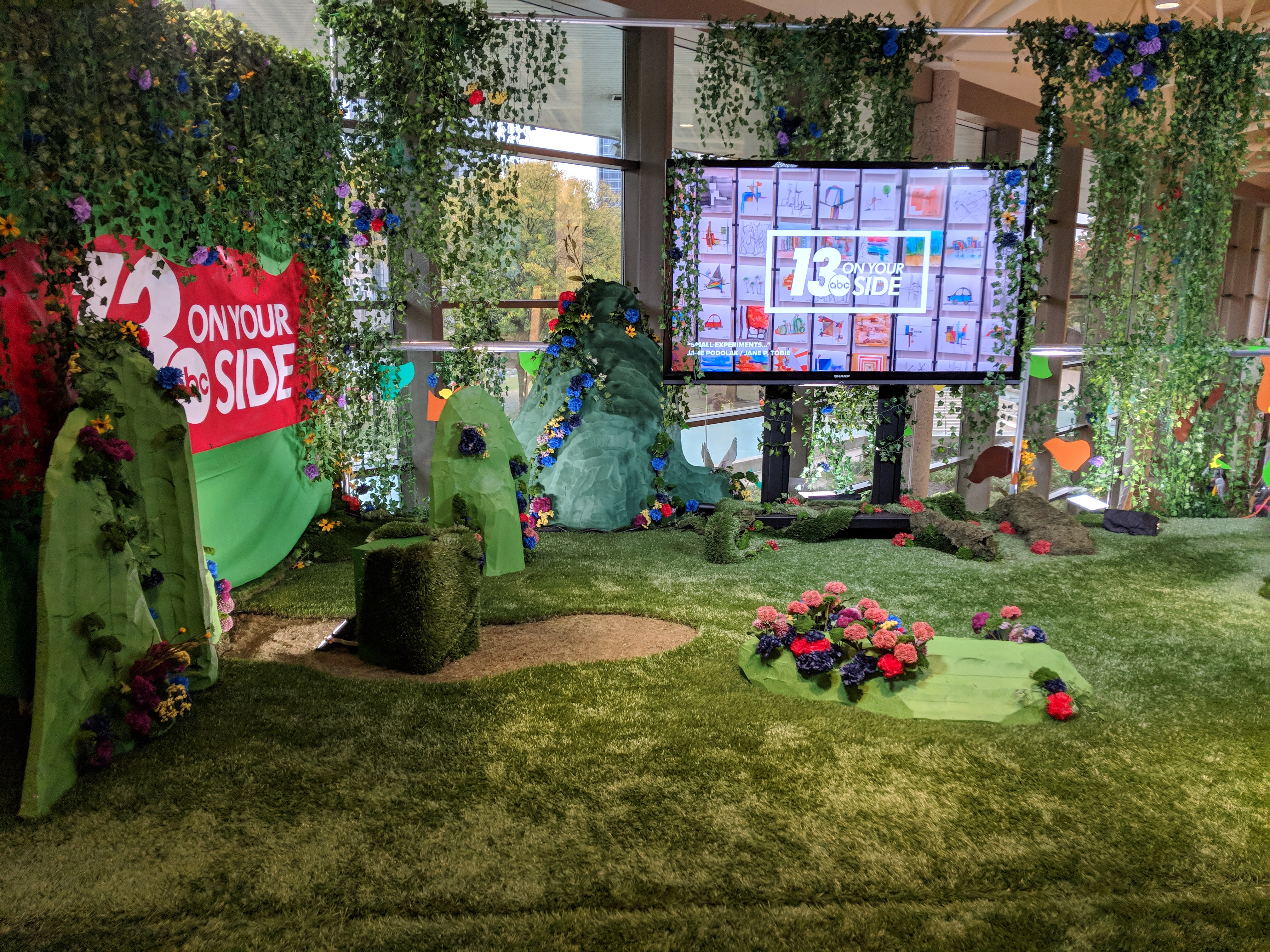 a broadcast television news set decorated with fake floral and fauna