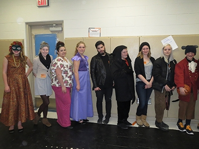Fashion Studies students posing next to the costumes they designed.