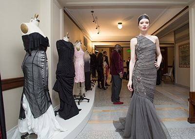 New York City fashion model Valeriya models a Pamella Roland gown next to a display of student-produced designs