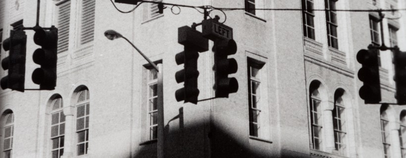 silhouette of traffic signals in front of against building