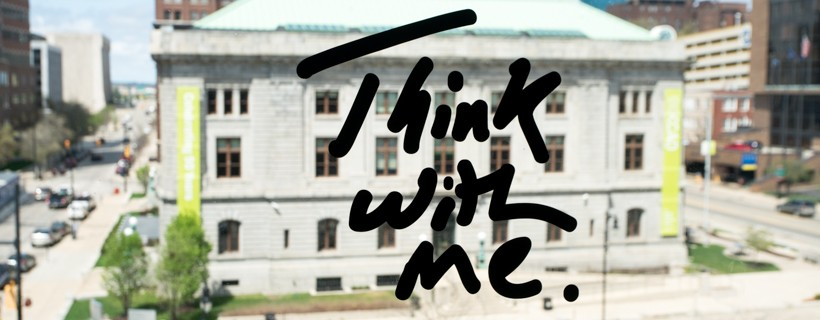 the words think with me on glass over a building seen in the background