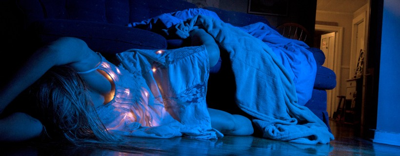 Photograph of figure bathed in blue light who has fallen onto the floor from a sofa
