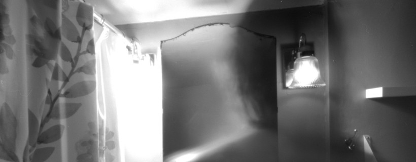 black and white photo of bathroom with ghostly figure