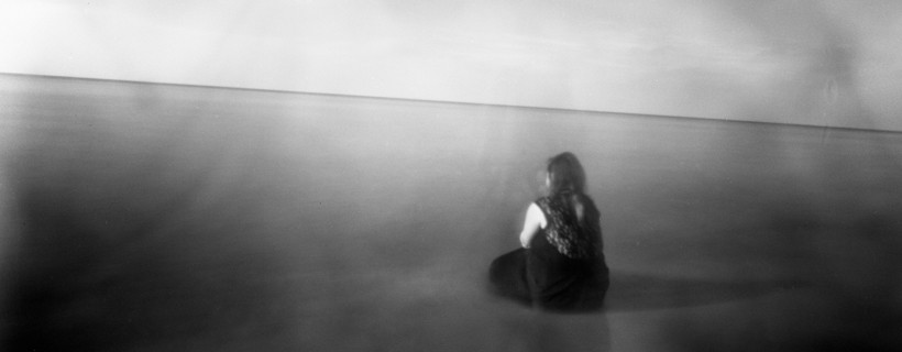 Foggy black and white image of woman sitting on surreal flat plane