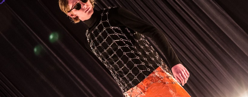 model wearing Black shirt with metal chain overlay and red pants