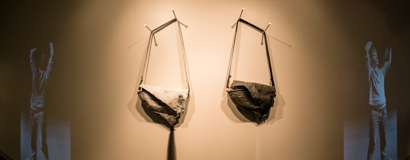 Installation piece featuring two bags hanging on the wall with projections on the wall on either side