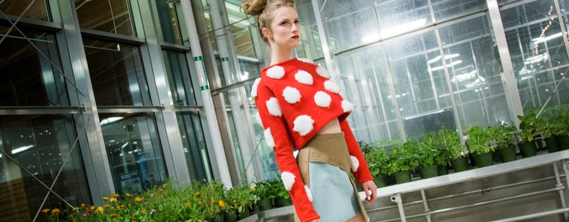 model wearing Red sweater with white fluffy balls on it with blue and tan skirt