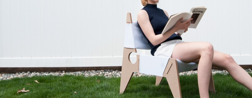 Chair on lawn with figure sitting on it and reading a book