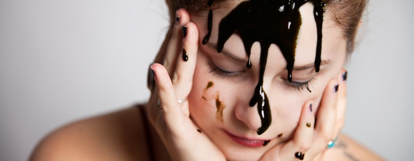 Image of figure with black liquid on their face