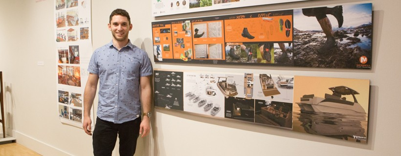 man standing next to examples of his design