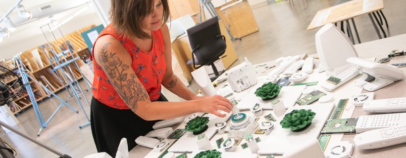 woman assembling white painted electronics and fake plants