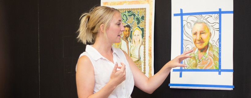 woman gesturing to colored pencil portrait on wall